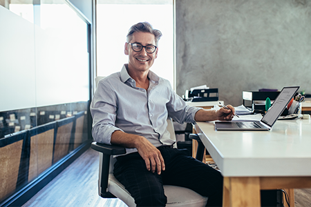 smiling male business owner sitting at desk with laptop
