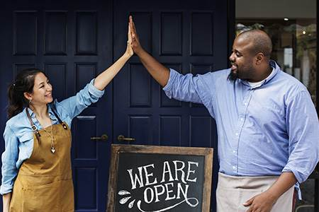 smiling male and female cafe owners sharing a high-five over their We are Open sign