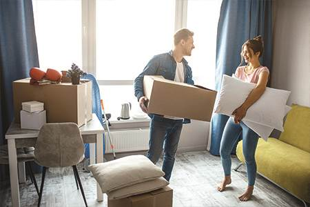 happy man and woman standing in living room unpacking moving boxes