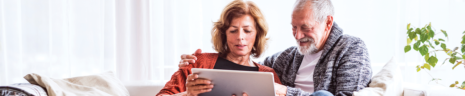 Mature husband and wife looking at IRA account on laptop at home