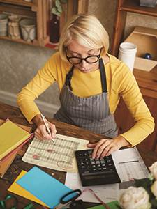 senior female business owner sitting at desk with calculator balancing business receipts