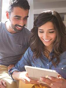 happy man and woman sitting together looking at marine bank mortgage rates on mobile device