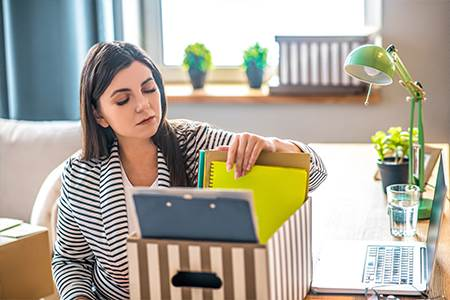 woman sitting at desk at home with laptop going through file box