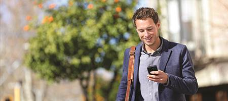 man dressed for work walking outside holding mobile device to check accounts using digital banking app