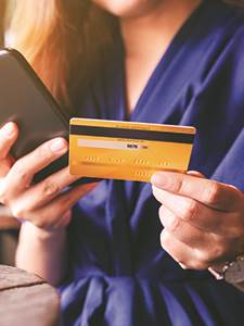 female holding credit card in one hand and holding mobile device in another