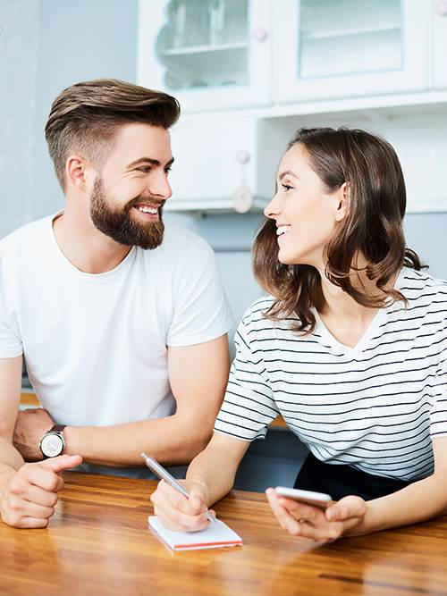 happy man and woman in kitchen looking at checking account options on mobile device