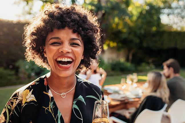 Smiling woman at outdoor dinner with friends