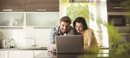 man and woman in kitchen on laptop using digital banking securely