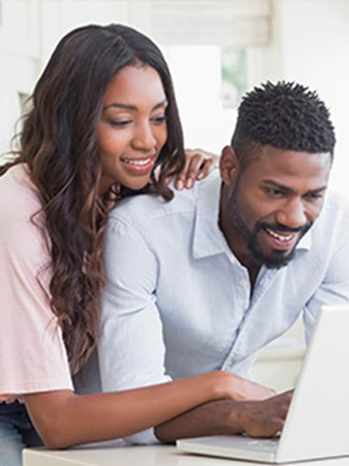 smiling man and woman standing at kitchen table looking using laptop to check out marine banks online home buyer tools