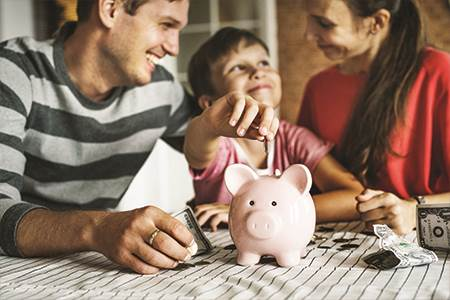 mom dad and son together talking about savings while child is putting money in piggy bank