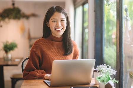 happy woman in front of laptop looking for savings account