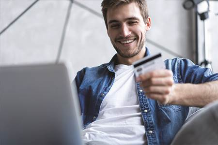 young man sitting on couch at home holding a credit card in one hand while looking at a laptop