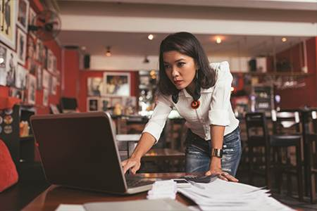 female busines owner leaning over table with a laptop in giftshop going through papers