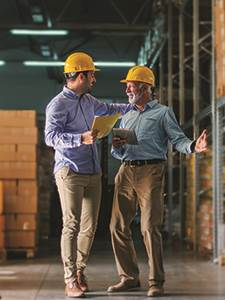two smiling men in a warehouse wearing hardhats