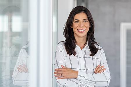 woman leaning against glass office door getting ready to meet her new lender