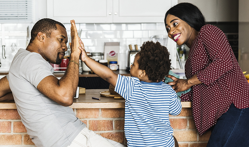 Dad and son high five with smiling mom